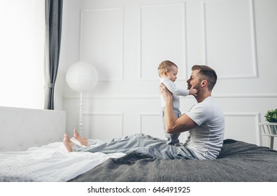 Happy father with his one year old son playing at home on the bed