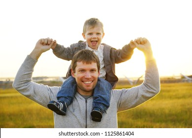 Happy father with his son having great time outside in the field, sun is shining