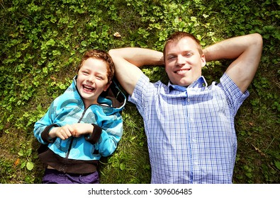 happy father and his son laying on the grass