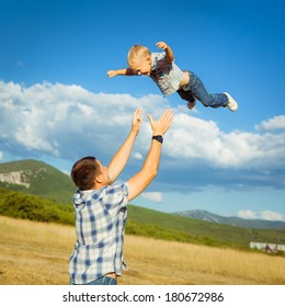Happy father and his son playing together. Outdoors. Fun. Smiling. Lifestyle. Family Vacation.