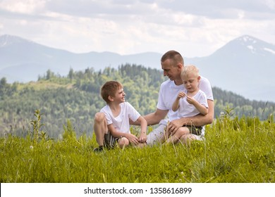 Happy father with his two young sons sitting on the grass on a background of green forest, mountains and sky with clouds. Friendship concept