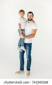happy father holding adorable little son and smiling at camera isolated on white