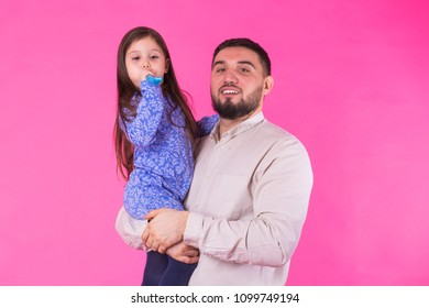 Happy father holding baby daughter in hands over pink background