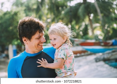 Happy Father Holding Cute Little Daughter on Tropical Beach in the water