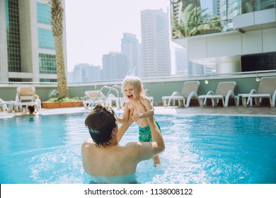 Happy father holding cute little daughter in the swimming pool