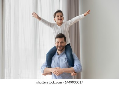 Happy father holding cute little son on shoulders, family having fun at home, funny activity game, excited smiling dad and adorable preschool child boy looking at camera, posing for photo