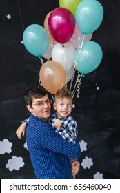 Happy father holding hes son on a black background with balloons