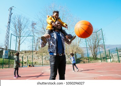 Happy father holding on shoulders his little son to help him to score a basket