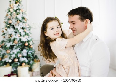 Happy father holds his little pretty girl in peach dress standing before a Christmas tree