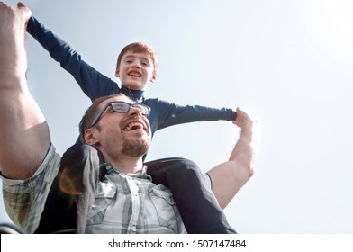 happy father holds his son on his shoulders