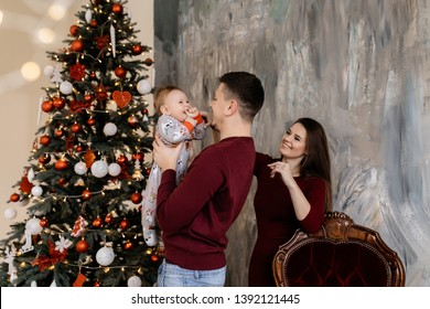 Happy father holds little baby near Christmas tree