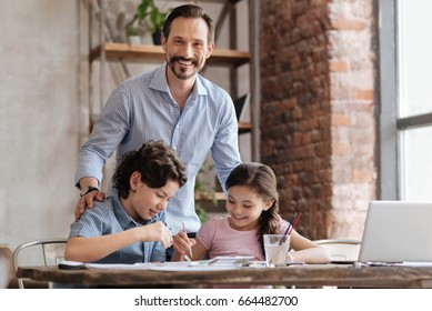 Happy father hugging his children while they painting