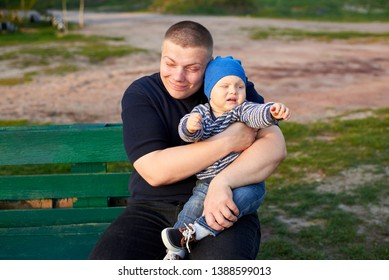 Happy father hugging his little angry son on a bench in the park