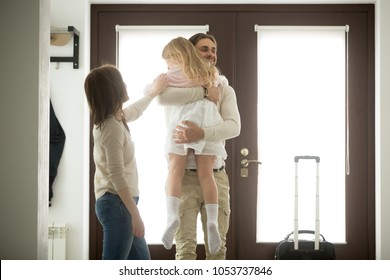 Happy father hugging little daughter arriving returning after long trip, smiling dad holding kid girl in arms embracing child standing in house hall, welcome back home daddy or family reunion concept