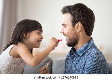 Happy father and kid girl laughing doing makeup together, little daughter puts lipstick on dads lips, funny child applying make-up on daddys face having fun playing enjoying time with parent at home