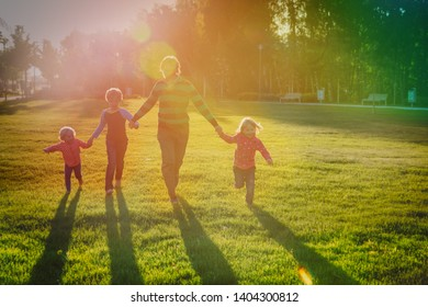 happy father with kids play in sunset nature