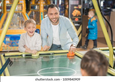 happy father with kids playing air hockey in entertainment center