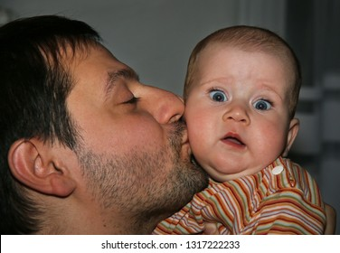 Happy father kissing his little baby daughter at home.