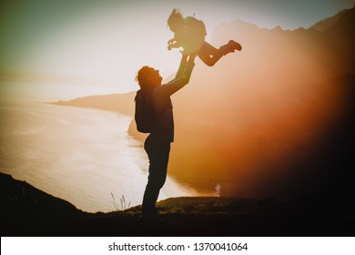 happy father and little daughter travel in mountains at sunset