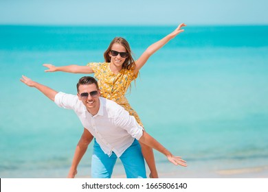 Happy father and little girl on white sandy beach have fun together