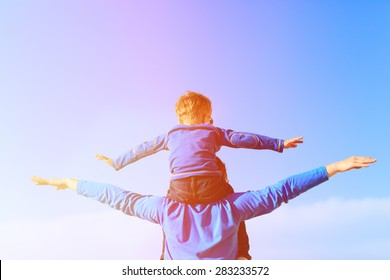 happy father and little son on shoulders play on sky