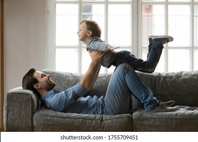 Happy father and little son playing funny game at home, loving happy dad carrying adorable preschool boy pretending flying with hands outstretched, lying on cozy couch in living room
