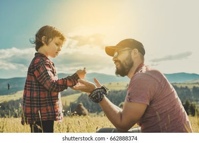 Happy father and little son are walking in the mountains