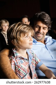 Happy father looking at son watching movie in cinema theater