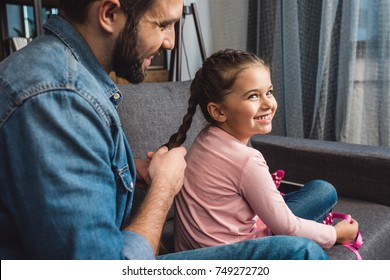 happy father making hair braid for daughter while sitting on couch at home