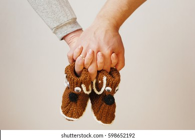 Happy father and mother hold in their hands baby shoes of their future first child