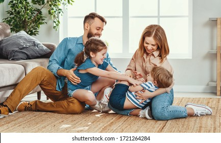 Happy father and mother with little children sitting on floor near sofa and laughing while having fun together at home during weekend