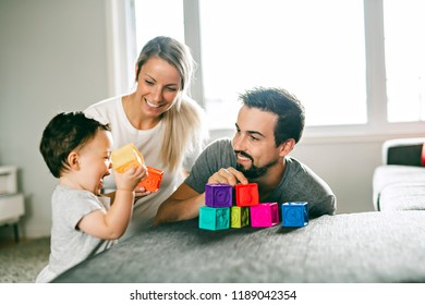 happy father, mother and little daughter playing with toy blocks at home
