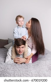 Happy father, mother, little son lies on grey bed in cozy bedroom, focus on man, woman kisses kid