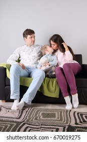 Happy father, mother, little son sit on couch in living room, boy kisses mother