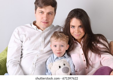 Happy father, mother, little son sit on couch with toy bear in room