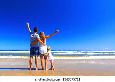 Happy father mother and little stand on the sea shore on a sunny day.COpy space, back view.