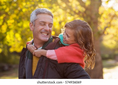 Happy father piggybacking daughter at park during autumn
