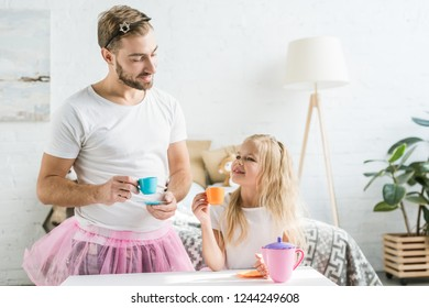 happy father in pink tutu skirt looking at cute little daughter pretending to have tea party at home