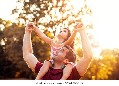 Happy father playing and carrying his daughter on shoulders in park.