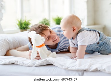 Happy  father playing with his  baby toddler in bed
