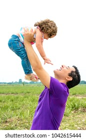 Happy father playing with his daughter outside. Dad holding baby girl toddler up in the air at outdoor. Fatherhood concept