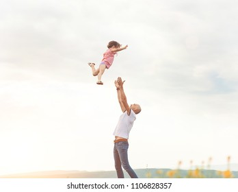 Happy Father playing with his daughter in sunny field on sunset. Summer happy family lifestyle, truly emotions. Little girl flying high in the sky from dad's hands