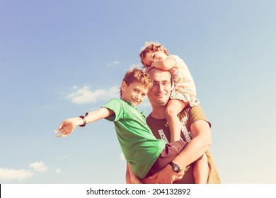 happy father playing with two kids outdoors