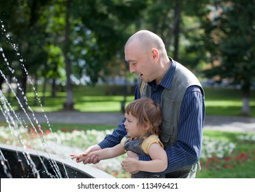 happy father plays with 2 years child in park