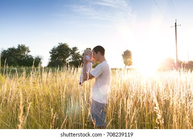 Happy father plays with his son at sunset. Family relationships