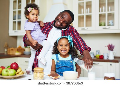 Happy father preparing breakfast for his daughters at home
