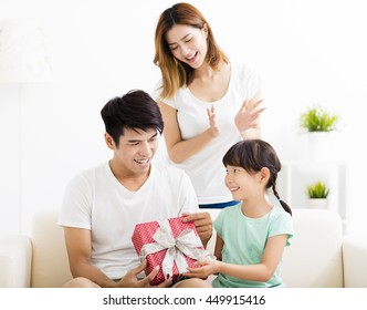happy Father receiving gift box from wife and daughter