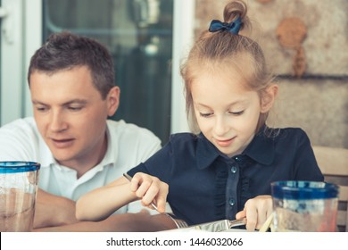 Happy father with small daughter eating in restaurant family lifestyle