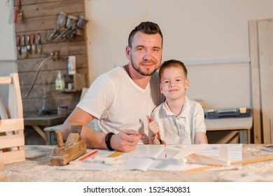 Happy father and son in the carpenter's home workshop making crafts from wood
