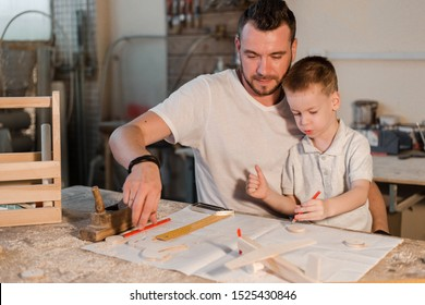 Happy father and son in the carpenter's home workshop draw drawings for future crafts made of wood
